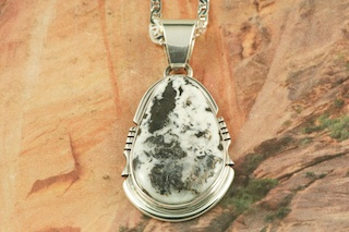 White Buffalo Turquoise set in Sterling Silver Pendant. This Beautiful Stone is formed from the minerals Calcite and Iron. It is mined near Tonopah Nevada. Free 18&quot; Sterling Silver Chain with Purchase of Pendant. Created by Navajo Artist Arkie Nelson. Signed by the artist.